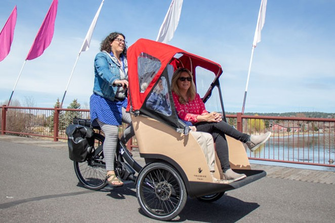 Courtney Van Fossan pilots an electric-powered tricycle taxi through the Old Mill District, with 90-year-old Leanne McConville and her care manager, Jennifer Rogers, in tow. - KEELY DAMARA