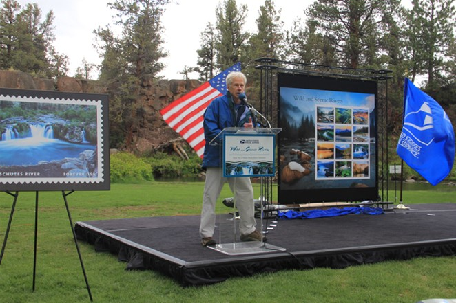 With American and United States Postal Service flags waving patriotically in the wind, Tim Palmer speaks about his passion for Wild and Scenic Rivers. To the far left, pictured on postage, is Steelhead Falls on the Deschutes River. - K.M. COLLINS