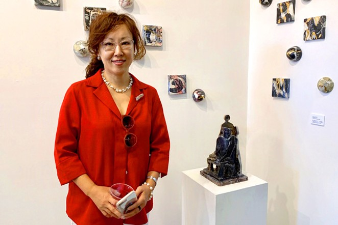 Shin Yeon Jeon stands with her work. - NANCY FLOYD