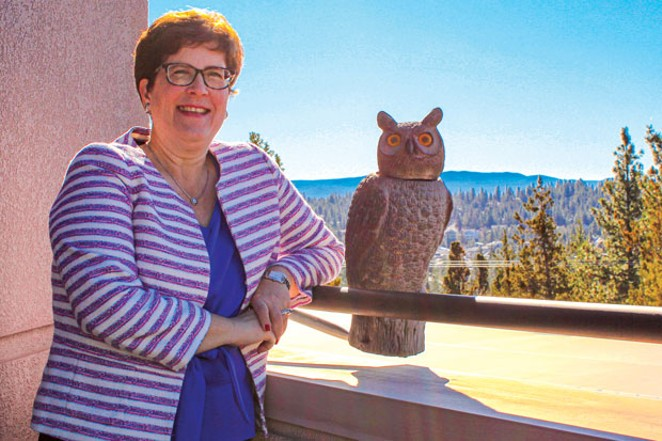"""Dr. Laurie Chesley, COCC's new president, stands with an owl decoy outside her office, which is meant to scare off—rather than attract—nearby birds. Chesley said her last community college campus in downtown Grand Rapids, Michigan, was urban, and did not have any deer or """"bunnies."""" - LAUREL BRAUNS"""