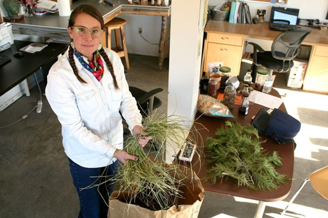 """Indigenous farmer Spring Olson, seen here inside her farm """"classroom"""" and workspace, opens a bag of sweetgrass, which has a variety of traditional medicinal and spiritual uses. - NICOLE VULCAN"""