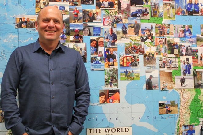 Local author and financial planner David Rosell has traveled to nearly 80 countries. He stands in front of a map of the world with photos of his fans reading his book while out on their own adventures. - LAUREL BRAUNS