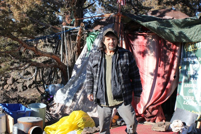 Jon Atkins stands outside of his tent at Juniper Ridge in northeast Bend, where he has lived for a year and a half. He said he has been continually denied disability claims and now has an attorney working on his behalf. He was not aware of the City's plans to move the camps at Juniper Ridge. - LAUREL BRAUNS