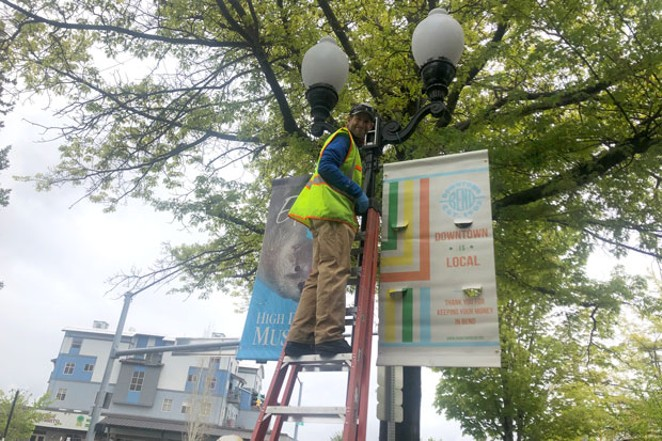 The Downtown Bend Business Association worked during lockdown to help its members change their business models and sell products online. Here, a DBBA staffer puts up new banners encouraging people to shop local. - NICOLE VULCAN