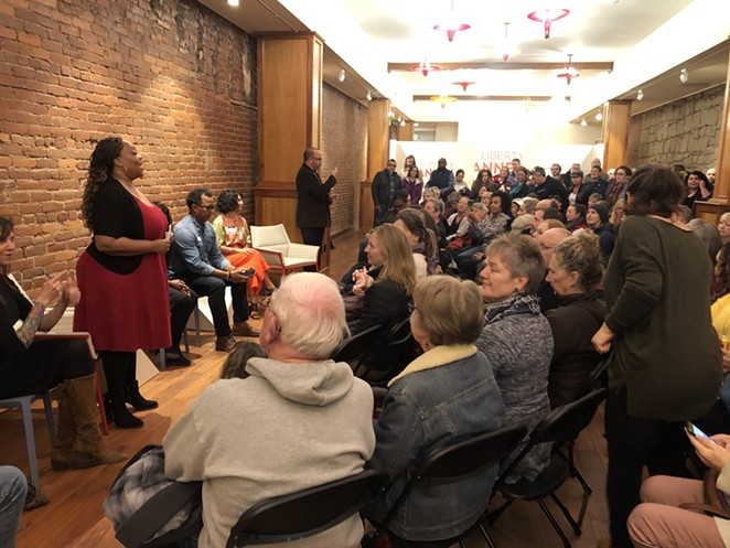 McCalpine addresses a packed room at the first Love Your Neighbor event at At Liberty Arts in downtown Bend in February 2020. - NICOLE VULCAN