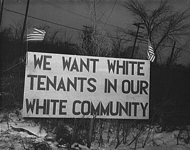 """Sign with American flag """"We want white tenants in our white community,"""" directly opposite the Sojourner Truth homes, a U.S. federal housing project in Detroit, Michigan. A riot was caused by white neighbors' attempts to prevent African American tenants from moving in. - HISTORICAL PHOTO FROM WIKIPEDIA"""