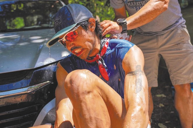 """Mario Mendoza, Jr. cools off during the """"Western States 100"""" race where temperatures were recorded reaching 104 degrees. He finished 16th out of 299 people. - PAUL NELSON"""