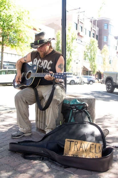 """Traveling street performer """"Wade,"""" left,  stops by to play on the corner of Bond and Minnesota. Wade, not being a local, was only passing through Bend. - KYLE SWITZER"""