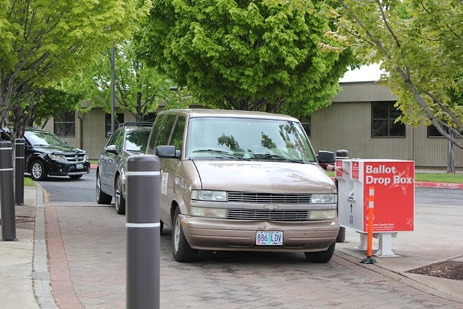 A line of cars forms behind one of Bend's busiest ballot drop box sites at the Deschutes County Clerk's office at 1300 NW Wall Street. - LAUREL BRAUNS