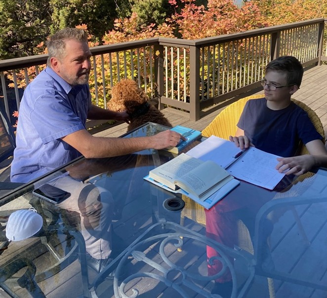 Jason Tierney, the founder of Central Oregon Educational Pods, helps Grayson Graham with distance learning on an outdoor patio. - COURTESY OF JASON TIERNEY
