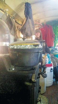 Cindy Looney's woodstove and cook setup with her son in the background. - CINDY LOONEY