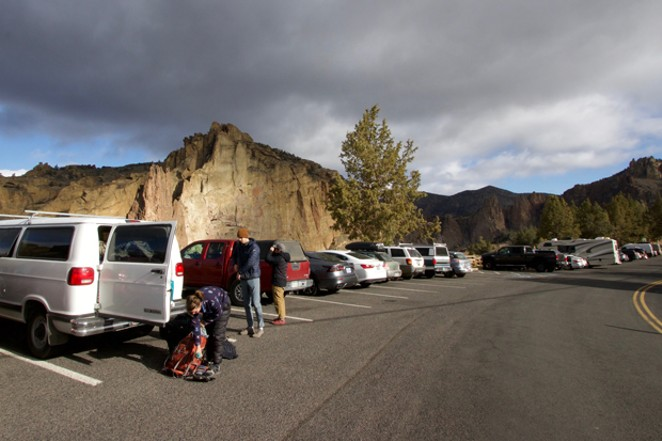 Emily Johnson, left, Darren Redden, center, and Tim Han, prepare for a day of climbing at Smith Rock State Park April 10. They arrived early to snag a parking spot on the weekend. Local law enforcement has been cracking down on cars parked illegally along the nearby roads, carrying fines of up to $115. - DEREK MAIOLO