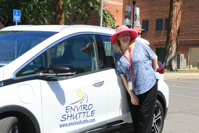 Milinda Calidonna poses in front of an Enviro Shuttle Prius. Melinda and her husband Bill said they've been working long days for months as they struggle to hire all the drivers they need. - JACK HARVEL