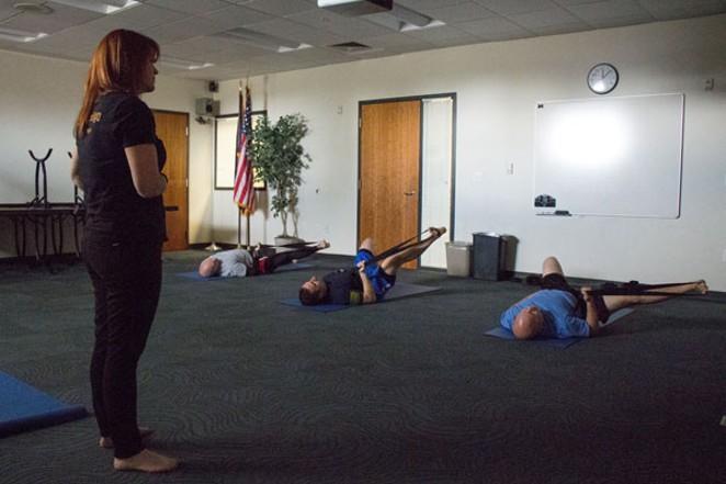 Christina Davenport leads Bend patrol officers through noontime yoga. - KEELY DAMARA