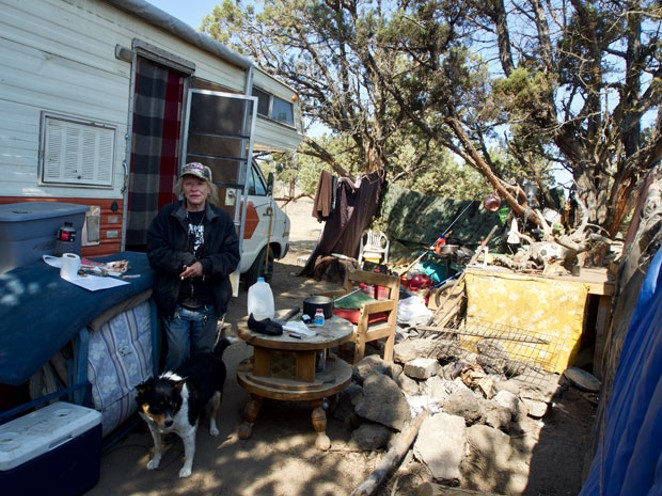 Debbie and her dog Little Joe stand in front of their RV on COID property on Tuesday, June 5. - CHRIS MILLER