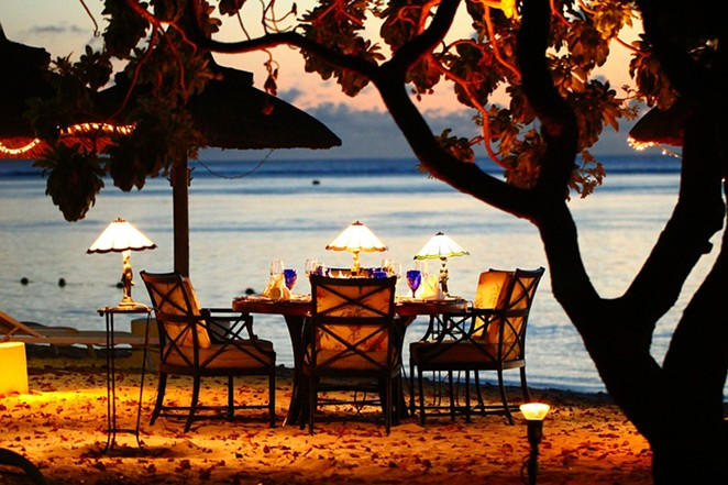 A candle-lit dinner overlooking the water. - PIXABAY