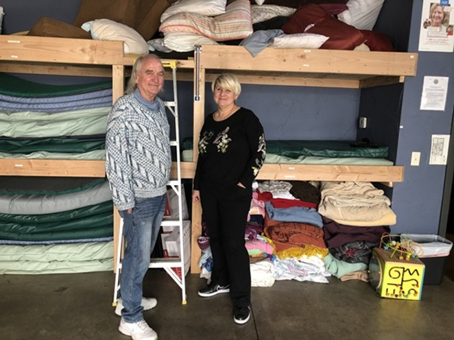 Larry Kogovsek and Sally Pfeifer stand in front of the newly-constructed bunk beds in the Sagewood Sanctuary, located inside Pfeifer & Associates on NW Greenwood Ave. Sagewood is currently the only approved emergency shelter in Bend. - NICOLE VULCAN