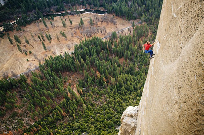 Tommy Caldwell chalks up his hands on a rock face. - IMDB.COM