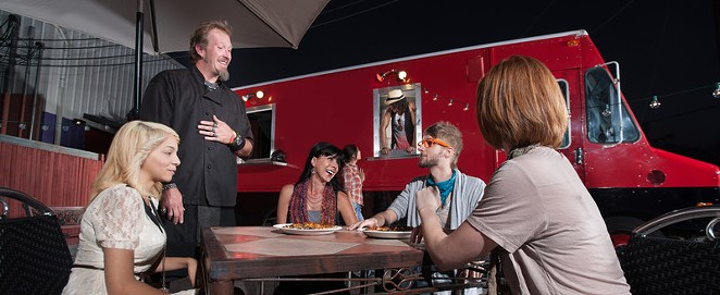 People eating at a food truck lot. - CANSTOCKPHOTO.COM