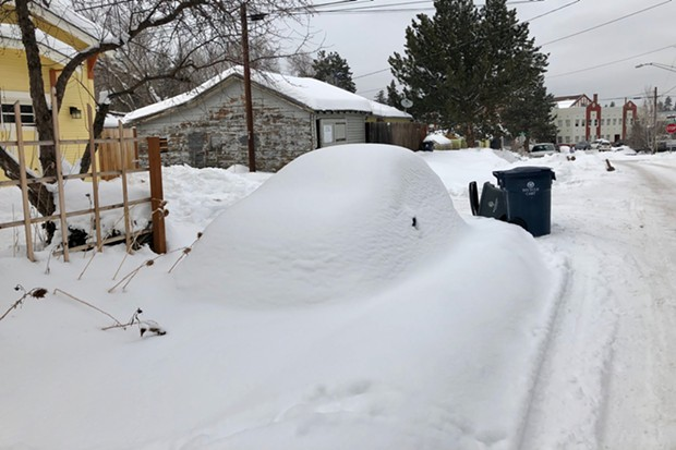 A car sits completely buried in the snow near downtown Bend. - CHRIS MILLER