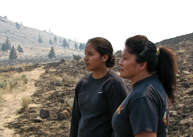 Karlen Yallup (left) and her mother Yvette Leecy, both firefighters, look out over a singed Warm Springs.