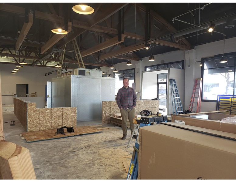 John Heylin stands in the space that is slowly being transformed into Unofficial Logging Co., Bend's first hatchet-throwing bar. - CAYLA CLARK