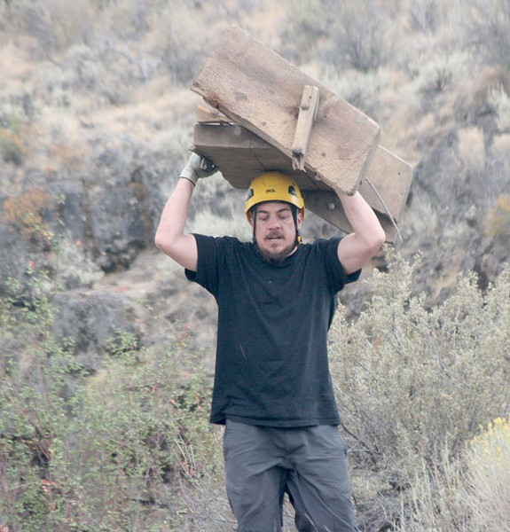 Greg Harshman carries ladder debris to the top of the ice cave trail. - GINGER SANDERS