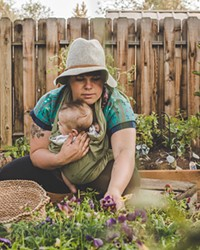 With her son, Forest, in a sling, Nickol Hayden-Cady harvests goodies from her garden.