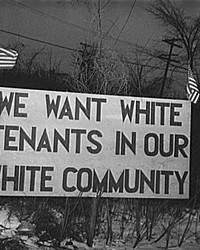 """Sign with American flag """"We want white tenants in our white community,"""" directly opposite the Sojourner Truth homes, a U.S. federal housing project in Detroit, Michigan. A riot was caused by white neighbors' attempts to prevent African American tenants from moving in."""