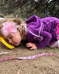 Liv, age 4, enjoys her first adventure via ants coming and going through a magnified looking glass.