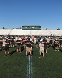 The Summit High School football team stands together to promote wearing a mask while working out. Although the football season is scheduled to start Feb. 22, the school's teams are already training in the weight room and doing conditioning exercises.