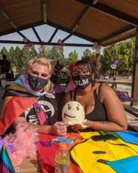 Activists create masks at a crafts table in Pilot Butte Neighborhood Park.