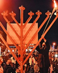 The event will look different this year (what doesn't in 2020?!) but the annual menorah lighting at the Old Mill is still happening this year, and slated for Thursday Dec. 10 at 4:30pm. The ceremony takes place in the westside parking lot across the Deschutes River from the shops, near the Hampton Inn, where people can watch the menorah lighting from their cars. After the lighting, the menorah will be placed in the Old Mill's Center Plaza, where it's been placed in other years—like the one seen here.