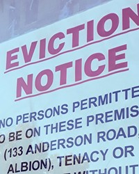 An eviction notice hangs in a window.