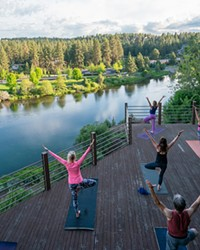 Yogis practice at the Haven Coworking patio space, perched on the cliffs above the Deschutes River.