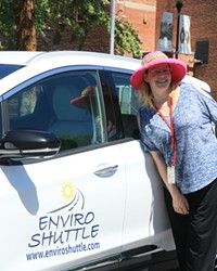 Milinda Calidonna poses in front of an Enviro Shuttle Prius. Melinda and her husband Bill said they've been working long days for months as they struggle to hire all the drivers they need.