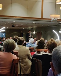 National Pulse Editor in Chief Raheem Kassam stands center stage in Bend Golf Club's dining hall on Wednesday, Aug. 25, for a sold-out fundraiser.