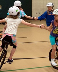 Four members of the Pine Ridge Elementary Unicycle Club practice riding in circles while holding hands.
