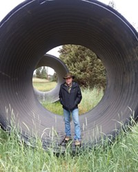 Brian Jennings stands inside an irrigation pipe.