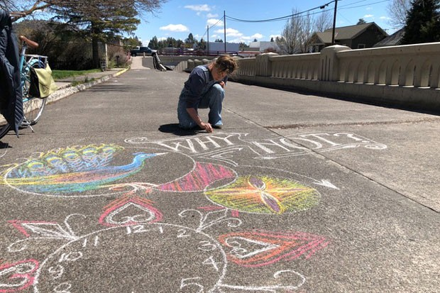 Kaycee Anseth takes advantage of the sunshine to draw with some chalk on the Franklin Underpass crosswalk. - TEAFLY PETERSON