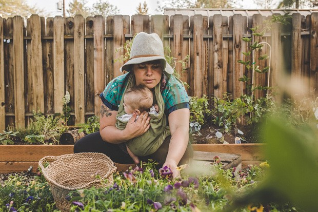 With her son, Forest, in a sling, Nickol Hayden-Cady harvests goodies from her garden. - TAMBI LANE PHOTOGRAPHY