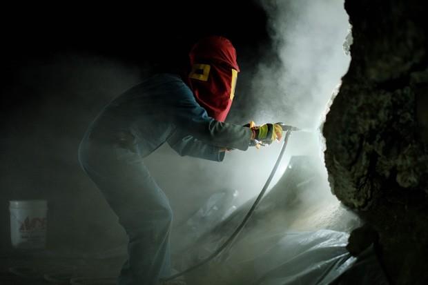 A volunteer sandblasts graffiti inside Boyd Cave. - DREW PICK