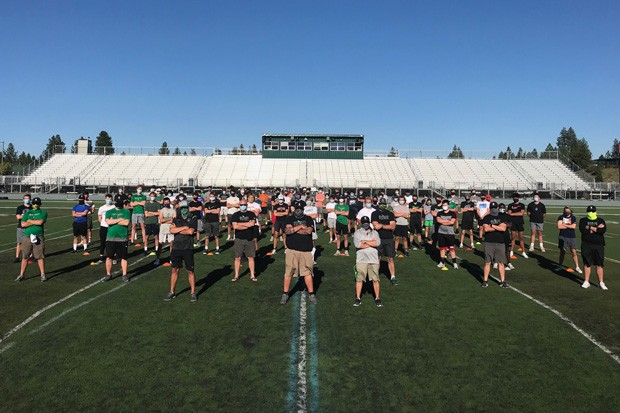 The Summit High School football team stands together to promote wearing a mask while working out. Although the football season is scheduled to start Feb. 22, 