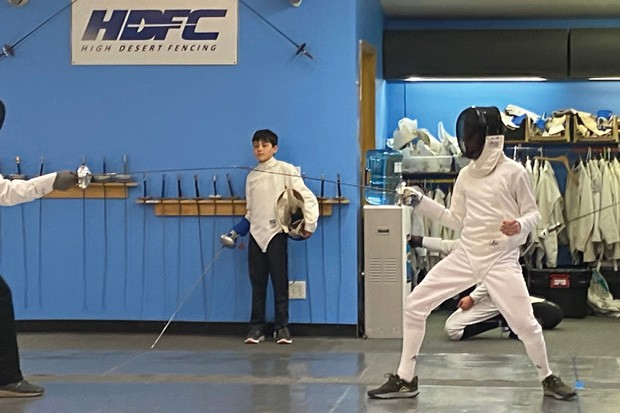 """Jackson Crocker works the piste, a magnetized mat that detects fencers' """"touches."""" - ALYCE PEARCE"""