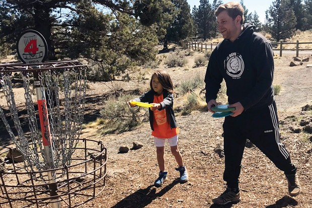 Father and son, John Bellman and Nyjah Sulesky enjoy time together playing Disc Golf at Pine Nursery Park. - NICOLE BLUME