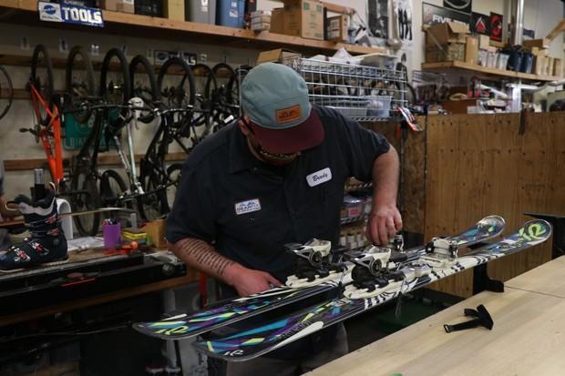 Brady Sherwood repairs a set of skis at Gear Fix. - TREVOR BRADFORD