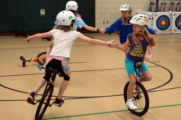 Four members of the Pine Ridge Elementary Unicycle Club practice riding in circles while holding hands. - CHRIS MILLER