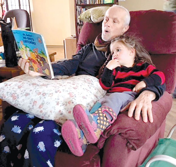 Brad Smith doing what he liked to do best; reading to his granddaughter, Hazel. - CYNTHIA CLARIDGE