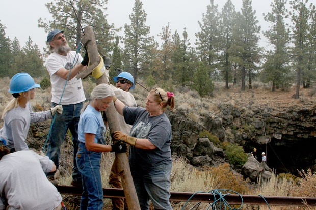 Brent McGregor, Kara Michelson and Ginger Sanders (center) work with volunteers and USFS personnel removing the defunct wooden ladder installed in the cave in the early 1960s. - JIM ANDERSON