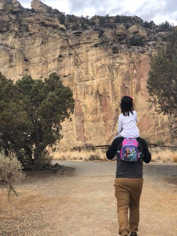 Carlos, an asylum seeker from Honduras, explores Smith Rock State Park in October with his young daughter riding on his shoulders. - SUE NELL PHILLIPS